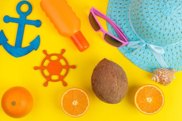 夏のアクセサリー。ビーチアクセサリー。日焼け止め、帽子、ココナッツ、オレンジ、メガネ