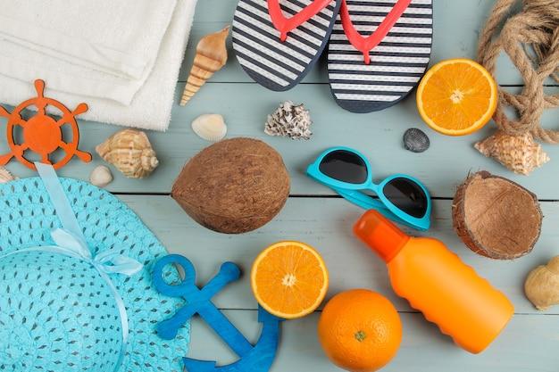夏のアクセサリー。ビーチアクセサリー。青い木製のテーブルに日焼け止め、帽子、貝殻、サングラス。上面図。