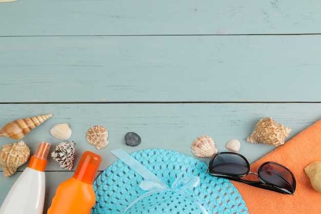 Summer accessories. beach accessories. sunscreens, a hat, shells, and sunglasses on a blue wooden table. top view.