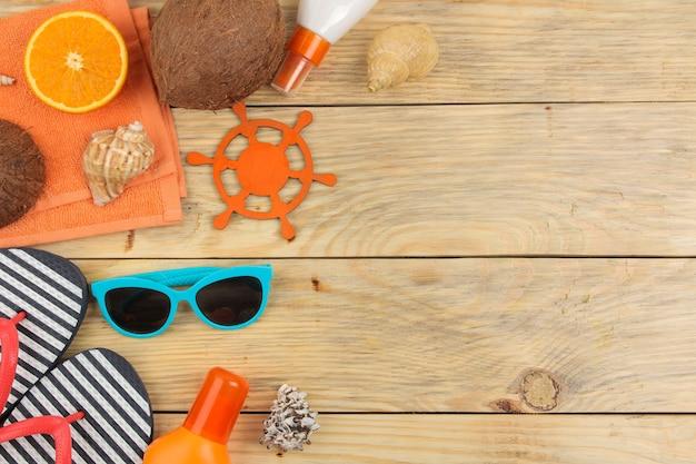 夏のアクセサリー。ビーチアクセサリー。日焼け止め、サングラス、ビーチサンダル、そして自然な木のテーブルにオレンジ。上面図。