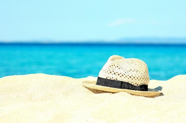 夏のアクセサリー:海岸の砂の上の帽子