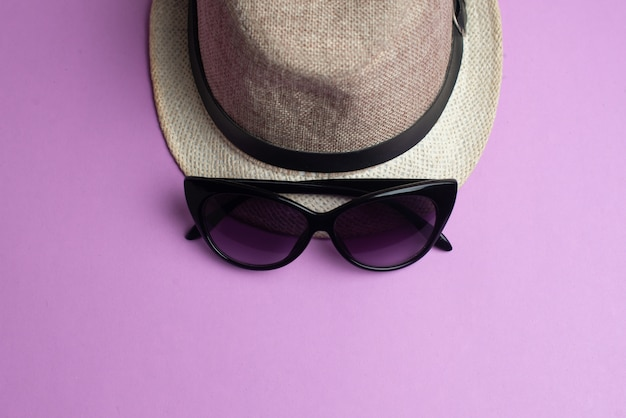 Summer accessories, hat and sun glasses on pink. summer vacation and sea concept.