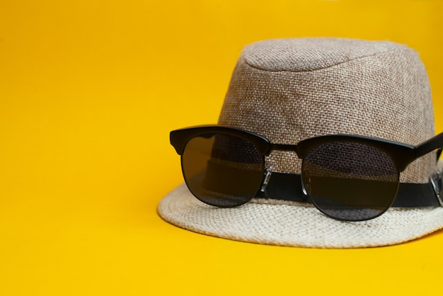 Summer accessories, panama hat and sunglasses on yellow