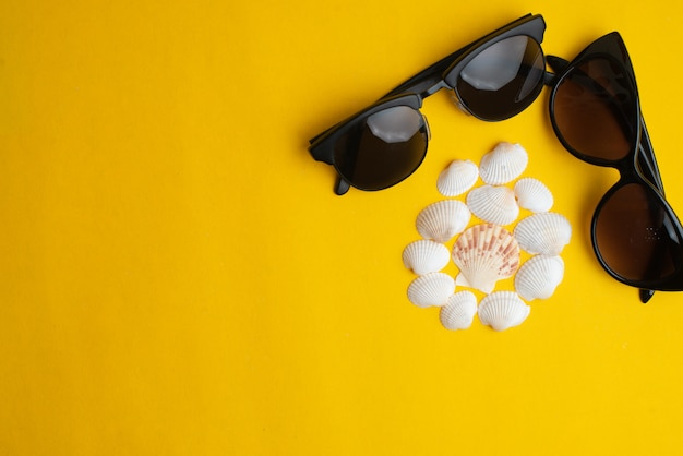 Summer accessories, shells and couple sunglasses on yellow surface.