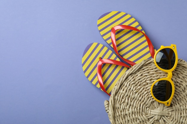 Summer accessories on violet isolated background, space for text