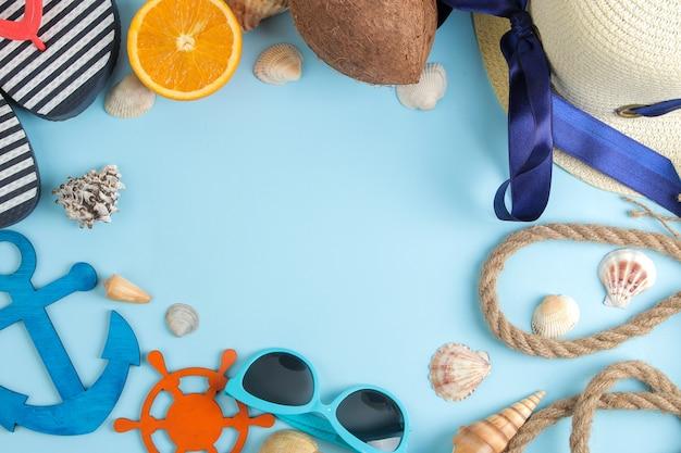 明るい青色の背景に、ココナッツ、オレンジ、サングラス、貝殻を使った夏のアクセサリー。上面図。