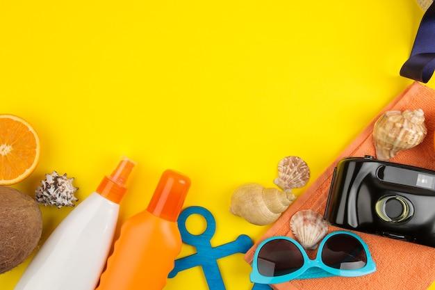 조개, 플립 플롭, 태양 안경, 밝은 노란색 배경에 카메라와 함께 여름 액세서리. 평면도.