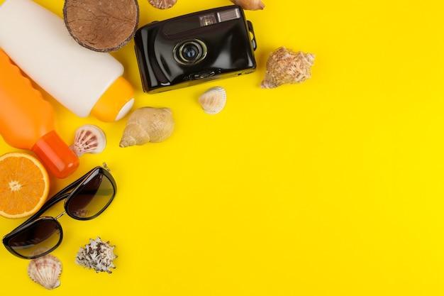 조개, 태양 안경, 밝은 노란색 배경에 카메라와 함께 여름 액세서리. 평면도.
