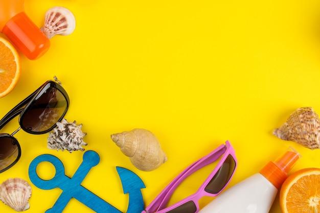 明るい黄色の背景に貝殻、サングラス、オレンジ、ココナッツを使った夏のアクセサリー。上面図。