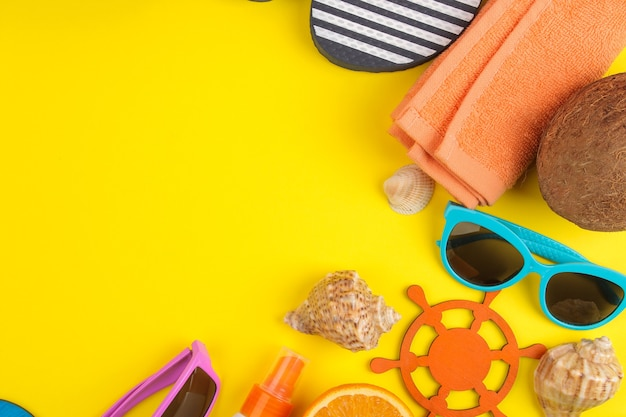Summer accessories with shells, sun glasses, orange and coconut on a bright yellow background. top view.