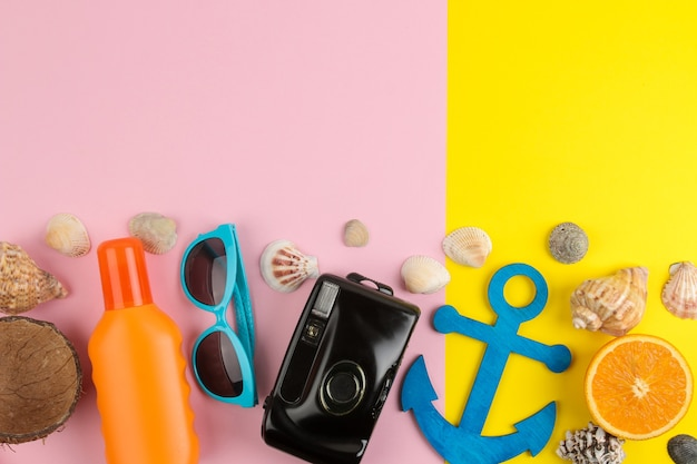 태양 안경, 모자, 조개, 플립 플롭, 밝은 노란색과 분홍색 배경에 카메라와 함께 여름 액세서리. 평면도.