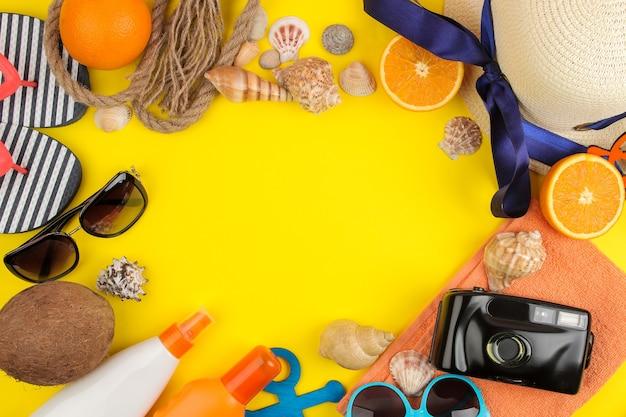태양 안경, 모자, 조개, 플립 플롭, 밝은 노란색 배경에 카메라와 함께 여름 액세서리. 평면도.