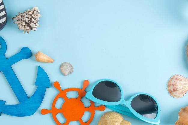 밝은 파란색 배경에 태양 안경 및 포탄 여름 액세서리. 평면도.