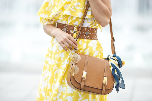 Летние аксессуары. женские аксессуары. дама в желтом платье. сумочка с косынкой и солнцезащитными очками.