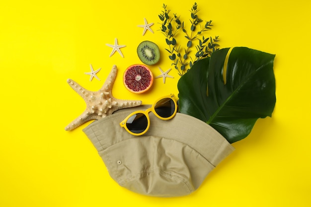 Summer accessories on yellow isolated background, top view
