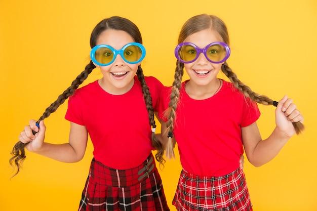 夏のアクセサリー。女の子のかわいい姉妹のような衣装は、夏のシーズンにカラフルなサングラスをかけています。黄色の背景にサングラスでポーズをとる子供たちのファッショナブルな友達。夏のファッショントレンド。夏の楽しみ。