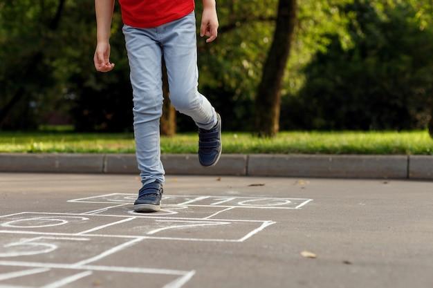 Summer activities for children. boy playing hopscotch.