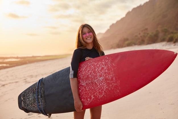Концепция летних мероприятий. довольная красивая молодая женщина, одетая в купальник, несет длинную доску, отдыхает за границей в курортной стране