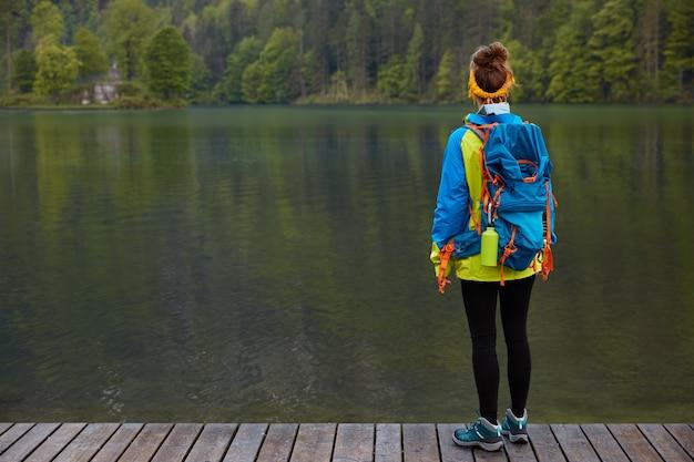 夏の冒険のコンセプト。ジャケットとスポーツシューズに身を包んだアクティブな旅行者の水平方向のショット