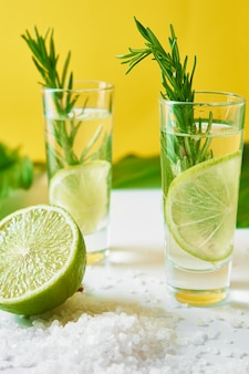 夏のアルコールカクテル。軽食レモンソーダドリンク。黄色の背景にライムとローズマリーのジントニック