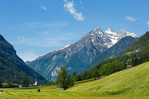 Летний вид на альпийские горы с травянистым лугом и дорогой в деревню (австрия)