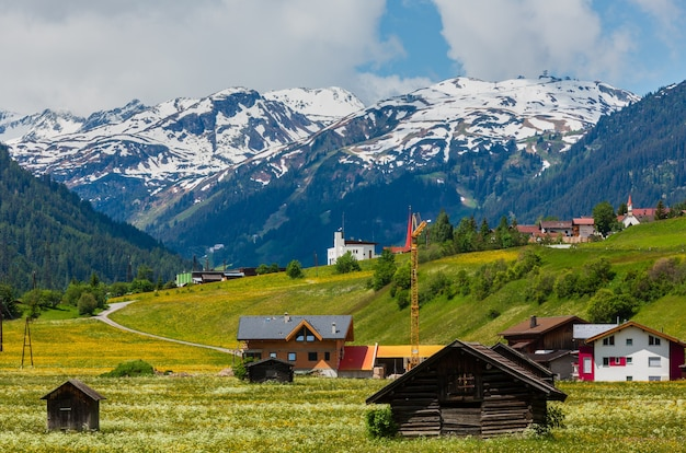 Summer alpine mountain country view with grassy meadow and road to village (austria)