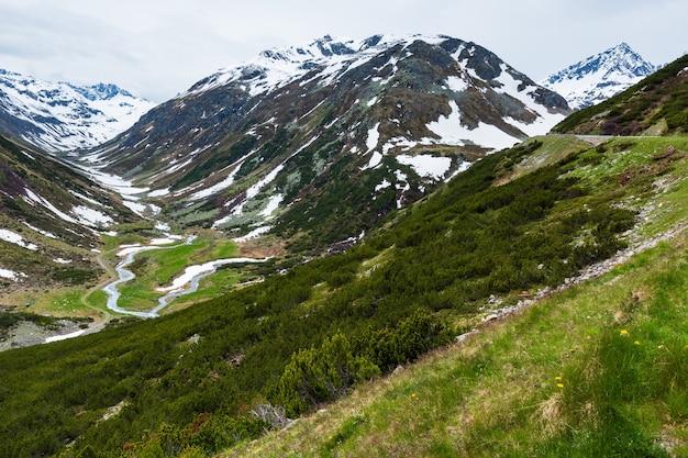 高山の道と川のある夏のアルプスの山の風景(スイス、フルエラ峠)。