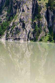 スイスの濁った貯水池と急な岩の斜面のある夏のアルプスの山の風景