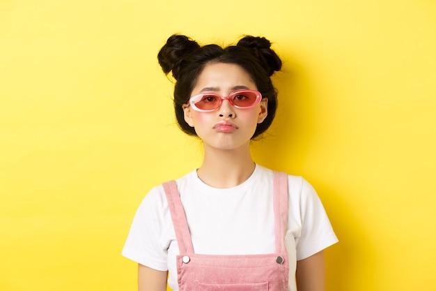 Концепция лета и моды. скучно азиатская девочка-подросток в солнцезащитных очках надувается, угрюмо стоя на желтом.