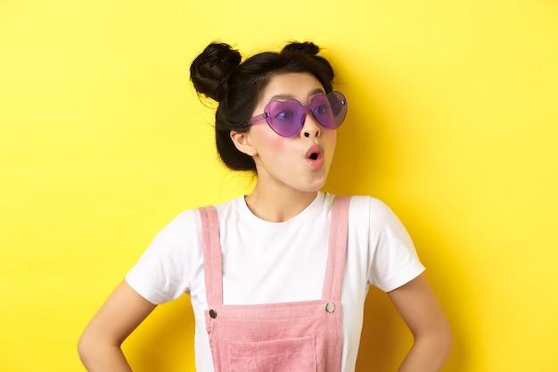 여름과 패션 개념. 노란색에 서 흥분된 얼굴로 오른쪽을 찾고 하트 모양의 선글라스에 놀란 아시아 십 대 소녀의 근접