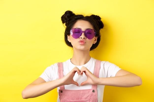 여름과 패션 개념. 선글라스와 헤어 스타일로 귀여운 글램 소녀, 키스에 대한 심장 기호와 주름 입술을 보여주는, 나는 당신을 사랑합니다 제스처, 노란색.