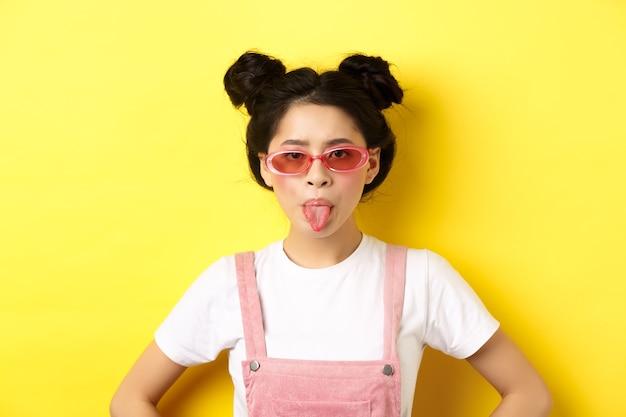 여름과 패션 개념. 어리석은 아시아 사춘기 소녀 혀를 보여주는 선글라스, 노란색에 서.