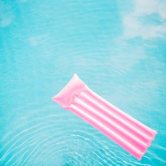 Концепция лета и бассейна с розовым матрасом