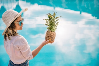 Summer and pool concept with woman holding pineapple