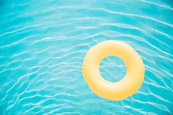 Summer and pool concept with yellow inflatable ring