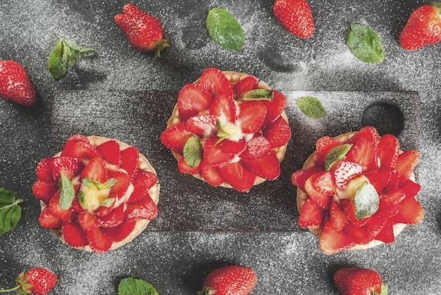 Летний и весенний десерт. домашние пирожки тарталетки с заварным кремом и клубникой, украшенные мятой и сахарной пудрой. на черном каменном столе, деревенский, с деревянной доской, поднос. copyspace вид сверху