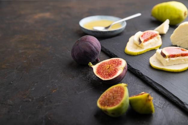 梨、カッテージチーズ、イチジク、蜂蜜と黒のコンクリートの背景にスレートボードの夏の前菜。側面図、クローズアップ、セレクティブフォーカス。