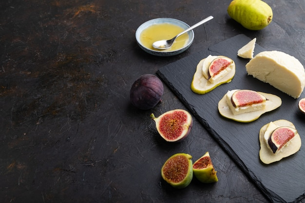 梨、カッテージチーズ、イチジク、蜂蜜と黒のコンクリートの背景にスレートボードの夏の前菜。側面図、コピースペース。