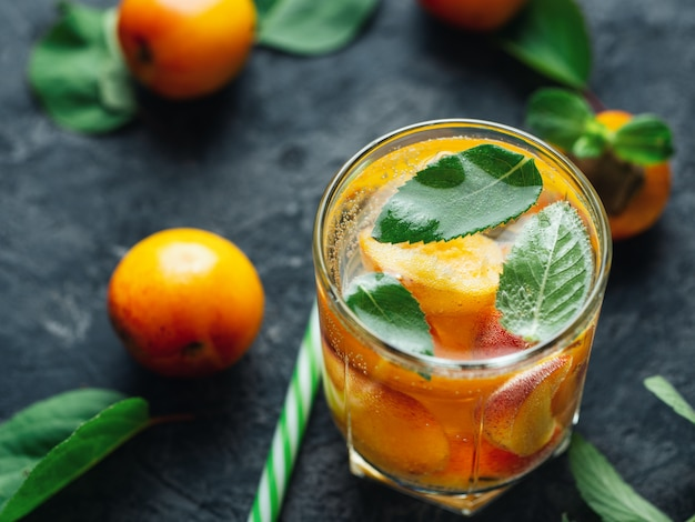 Summer apricot drink cocktail with pieces of fruit and mint