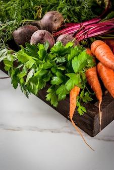 Лето, осенний урожай. свежие органические овощи фермы в деревянном ящике на белой мраморной столовой свекле, моркови, петрушке, помидорах.
