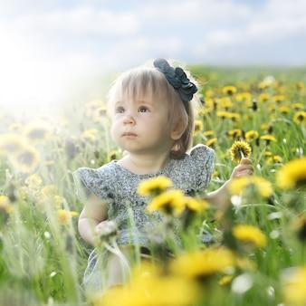 屋外の緑の芝生の上の夏の女の赤ちゃん