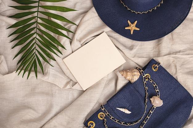 Летний фон синяя соломенная шляпа сумка из ракушек надпись книга пальмовый лист на текстильном льняном фоне