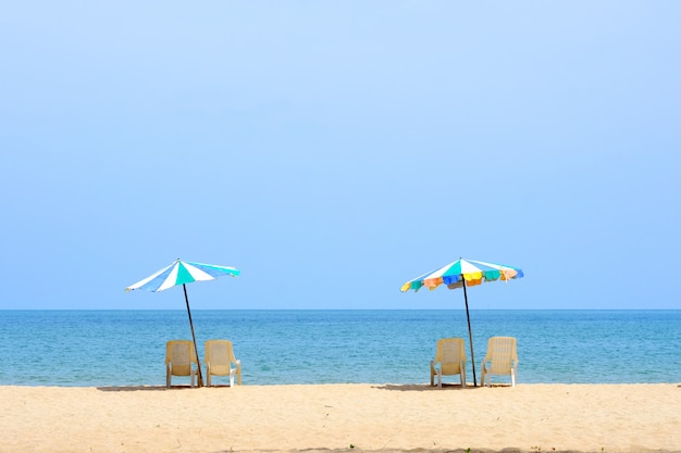 Summer background, chair and colorful umbrella on beach and sea background