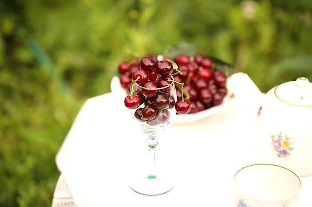 Летний фон вишня в стакане на столе в саду, деревенский стиль