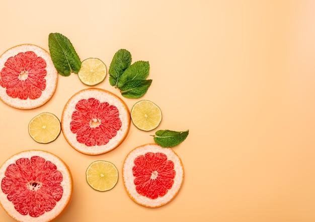 夏の背景コンセプトスライスグレープフルーツ、ライム、オレンジ色の背景にミント