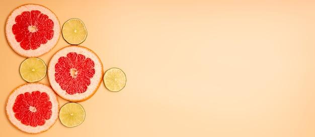 夏の背景コンセプトスライスグレープフルーツ、オレンジ色の背景にライム