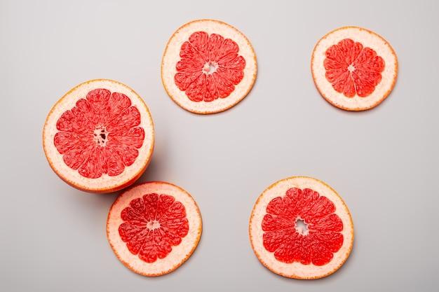 夏の背景の概念:スライスしたグレープフルーツ、灰色の背景にミント
