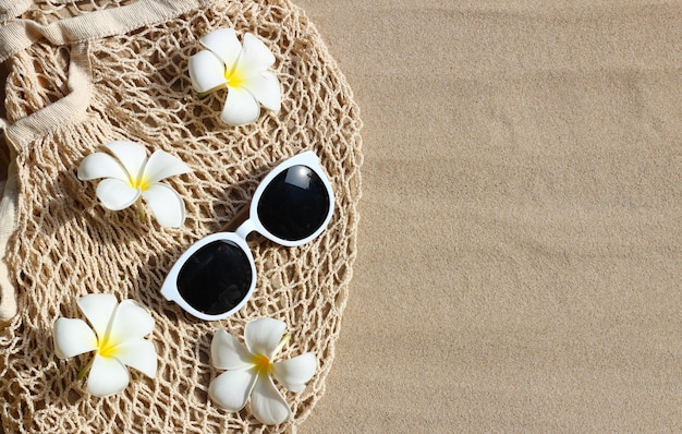 여름 배경 개념입니다. 모래에 메쉬 비치 가방에 흰색 plumeria 꽃과 선글라스.