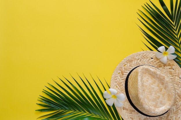 Summer background concept with beach hat, coconut leaves and frangipani flowers on yellow background.