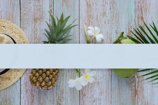 ビーチ帽子、パイナップル、ココナッツ、フランジパニの花と青い木製の背景とテキストの空白スペースと夏の背景の概念